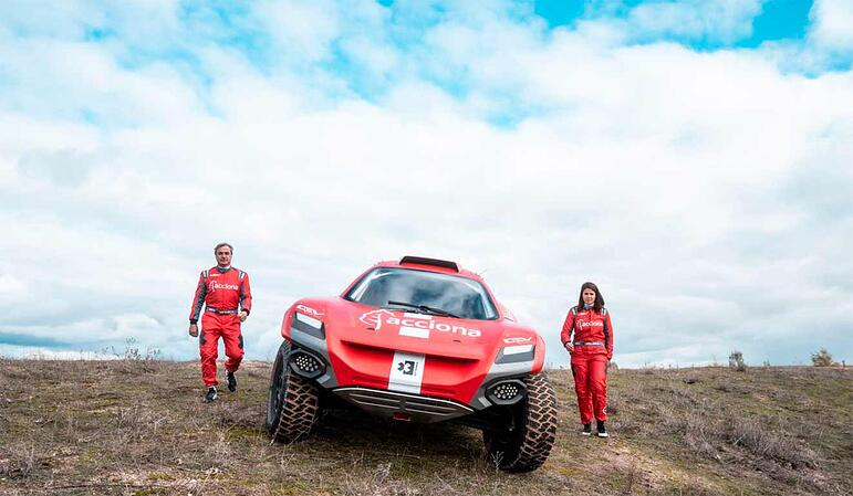 Racing red car with Acciona logo and two pilots